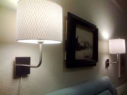 lighting bedroom with wall art and plug in wall sconce also