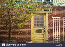 chicago illinois faded yellow wooden door red brick wall garden