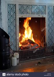 a victorian blue tiled fireplace with a roaring log fire fender