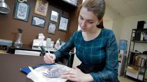 female tattoo artist drawing dinosaur sketch stock video footage