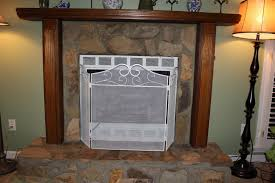 brown painted stone fireplace wrapped with glossed wooden mantel frame jpg