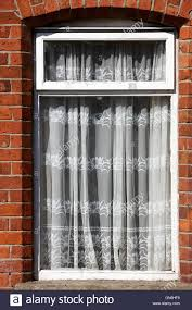 old net curtains hanging in the window of a red brick victorian