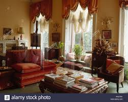 books on table in drawing room with red velour sofa and armchair