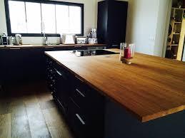 cuisine avec plan de travail en bois rangements sur un îlot central plan de travail en bois