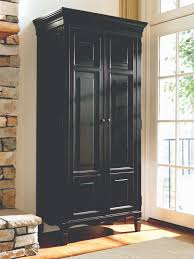 tall black wood stand alone storage cabinet with doors in corner