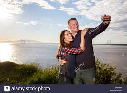 young couple using a smart photo to take a selfie at sunset point