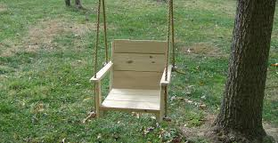 outdoor a wooden swing with a and a tree to the right and