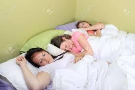 three pretty teenage girls sleeping on a bed at a sleepover or