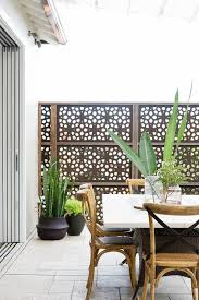 slat top outdoor dining table with modern white ladder back chairs