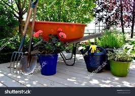 orange wheel barrow on deck garden stock photo 692537917