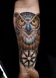 large illustrative style colored owl tattoo on forearm with