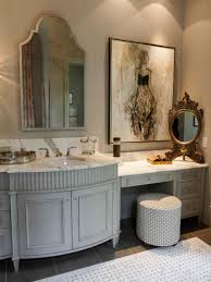 an ornate gold mirror complements the larger vanity mirror in this