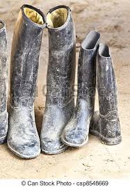 dirty riding boots dirty plastic riding boots standing at the muddy gry ground stock