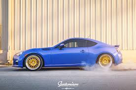 subaru stanced blue blue subaru brz wearing gold avant garde wheels wrapped in nitto