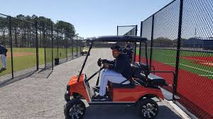 miguel cabrera drives a golf cart with chrome wheels around spring