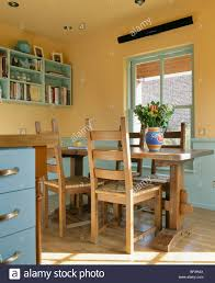 Yellow Dining Room Chairs Wooden Table Chairs In Yellow Country Kitchen With Blue Dado Stock