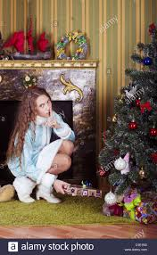nice teen in snow maiden costume put gifts under the tree