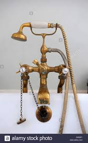 an antique brass mixer tap and shower head on a bath uk stock an antique brass mixer tap and shower head on a bath uk