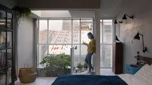 kc design studio adds perforated facade and atrium to skinny