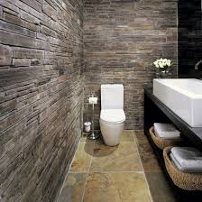 small bathroom with natural slate wall tiles and white fittings