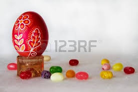 easter egg stands a decorated easter egg stands next to jelly beans on a white