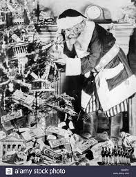 1930s uncle sam dressed as santa claus decorating christmas tree