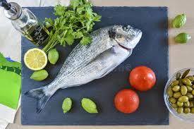 cuisiner cru un poisson cru prêt à cuisiner de brème avec le citron et les olives