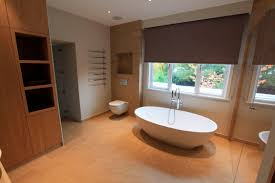 wood floor in bathroom oval white freestanding stone bathtub on brown ceramic floor plus