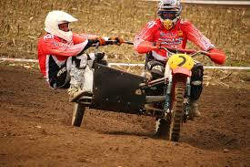 motocross bike trailer two riders riding on red and black motocross dirt bike with side