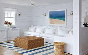white and blue beach bungalow living room with seagrass ottoman as