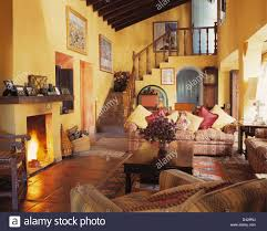 Yellow Fireplace by Comfortable Sofas In Yellow Living Room With Lighted Fire In Stock