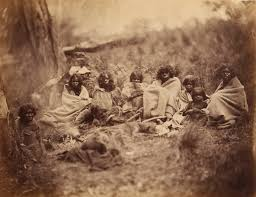 group of aboriginal women and children sitting in a bushland