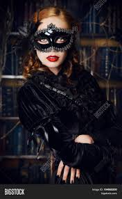 charming mysterious in black mask and black medieval dress