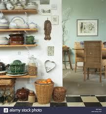 crockery on wooden kitchen shelves beside doorway to dining room