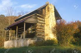 exterior of log cabin with fireplace and porch tn stock photo