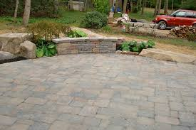 grey stone patio deck with stone bench plus green plant on yard of
