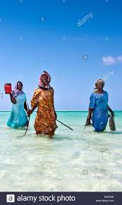brightly dressed women walking to the beach after fishing