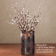 decorating lighted branches with white pot on wooden floor and