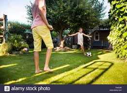 family playing soccer in summer with their children stock photo