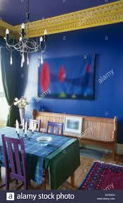 table with blue cloth and painted purple chairs in bright blue
