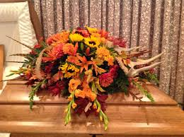 Casket spray of fall flowers and leaves along with pheasant feathers