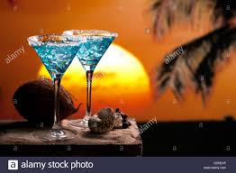 martini beach two blue cocktail on beach sunset palm tree coconut stock photo