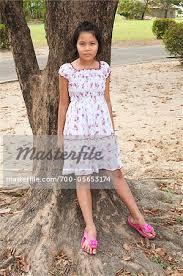 preteen thong girl leaning against tree bangkok thailand stock photo