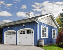front facing two car garage in white and light blue colors country house attached by a blue two car garage with white arched top door and upper