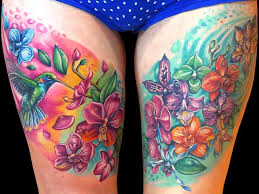 colorful flowers and hummingbird tattoos on both thigh