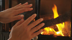 warm up the hands to the fire near the fireplace wood flame