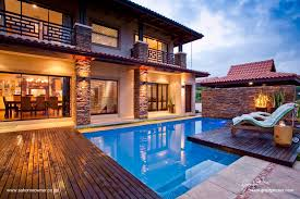 stone wall behind the pool and deck over hanging the pool is a