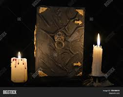 mystic still life with black magic book and two burning candles