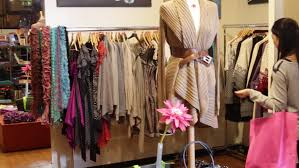 woman picking up dress and looking in mirror in clothing store