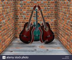 three guitars in the corner of the room with brick walls stock